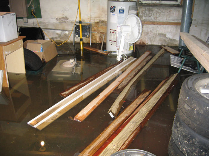 severely flooding basement in white city with lumber and personal