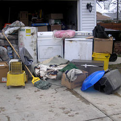 Soaked, wet personal items sitting in a driveway, including a washer and dryer in Melville.
